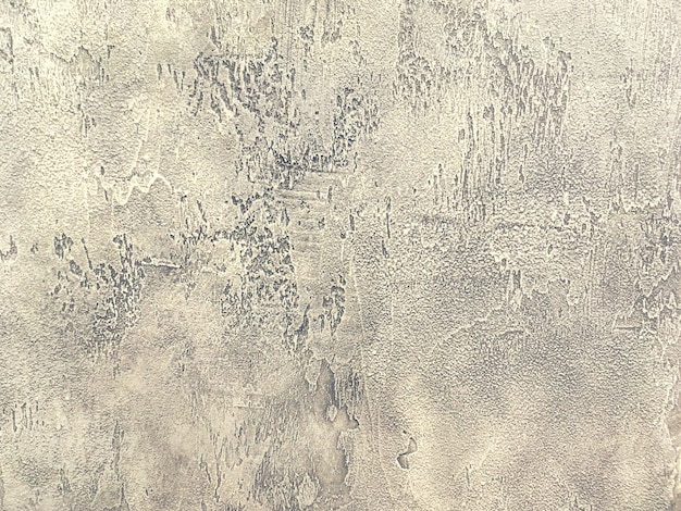 Old light brown wall covered with shabby uneven plaster