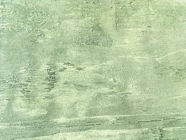 みすぼらしい石膏で覆われた古い薄緑色の壁。ビンテージオリーブ石表面の背景のテクスチャ