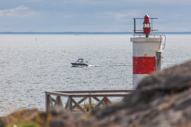 Old lighthouse and boat entering the sea gate in the baltic sea
