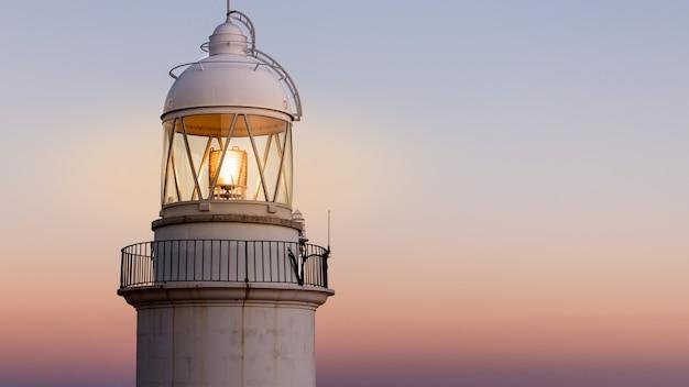 背景に美しい夕日と海岸の古い灯台