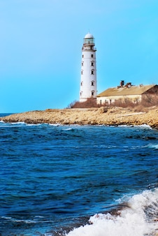 Старый маяк на берегу моря. буря, волны и голубое небо.