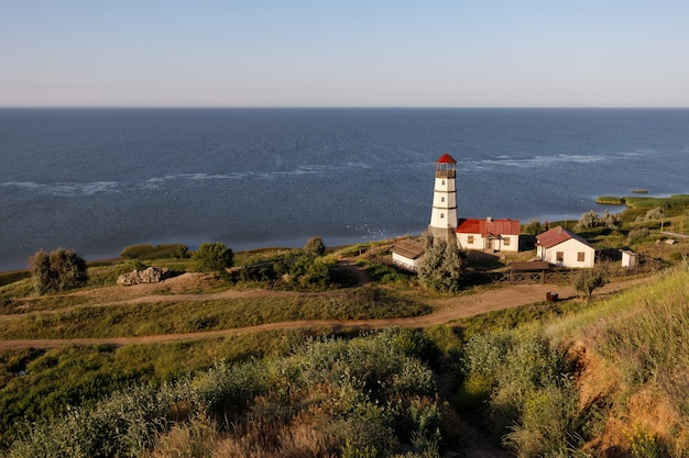Old lighthouse with a red roof on the sea shore in the morning.