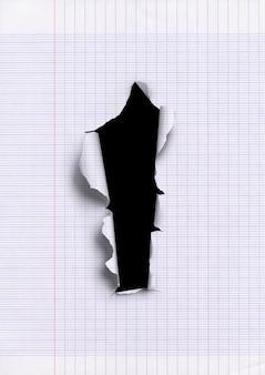 Старая линованная рваная бумага с отверстием.