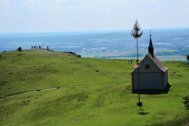 明るい太陽と小道の高い緑の丘にある古い小さな教会