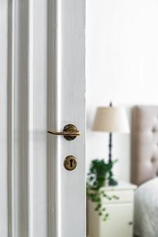 조명 아래 방의 흰색 나무 문에 오래 된 자물쇠와 손잡이