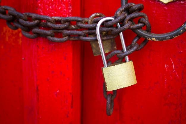さびた鎖を持つ木製の赤いドアにロックされている古いロックパッドをクローズアップ。