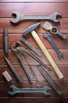 짙은 갈색 나무 배경에 있는 오래된 자물쇠 제조공 철 도구