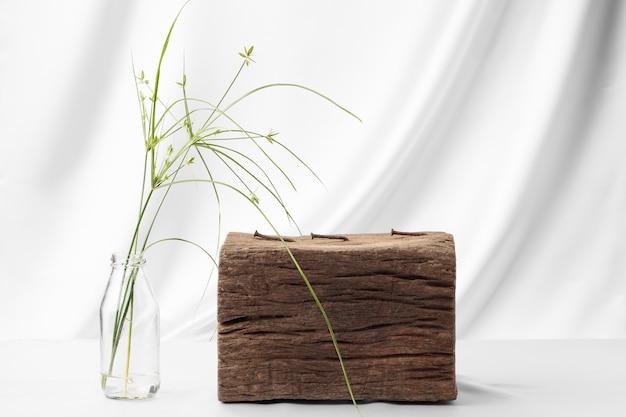 Старое бревно для размещения продуктов и цветов зеленой травы, оформленное в землистых тонах.
