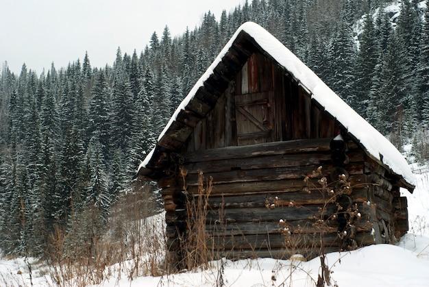 冬の森に覆われた山のふもとにある古い丸太狩猟小屋