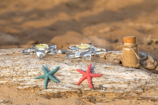 On an old log in the sand, starfish and sand in a bottle
