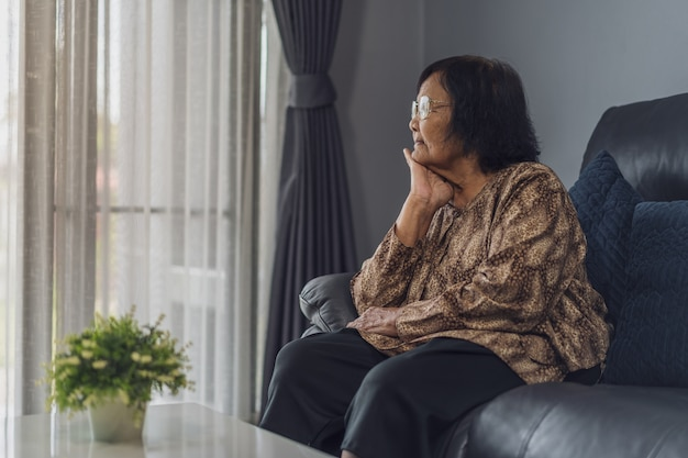 Old lonely woman sitting on sofa in living room