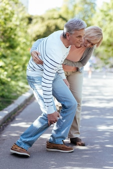 Old loving pleasant woman caring about ill husband and supporting him while standing in the park