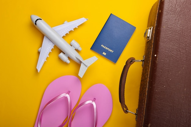 Старый багаж, шлепки, фигурка самолета, паспорт на желтой поверхности