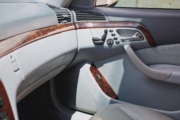 Старый роскошный интерьер автомобиля бежевого цвета с электронными кнопками
