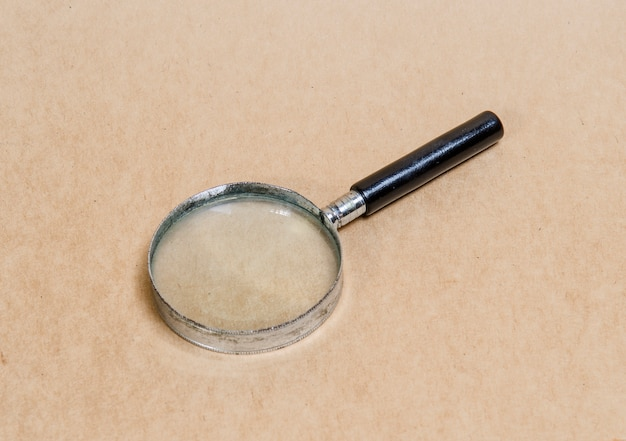 Old magnifying glass on vintage paper background