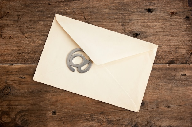 Old mailing envelope and sign the e-mail on a wooden background