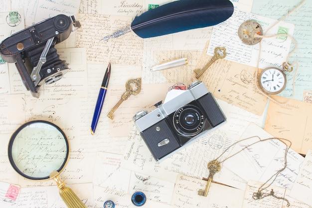 빈티지 시계, 깃털 펜, 카메라 및 키와 함께 오래 된 메일 배경