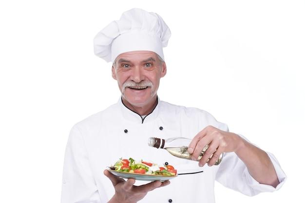 白い壁に野菜サラダと油のプレートを保持している老人男性料理人