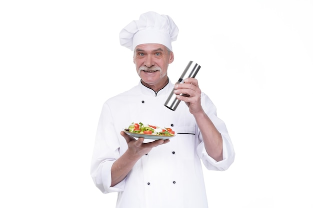 Old male cook holding a plate with vegetables salad and pepper on white wall