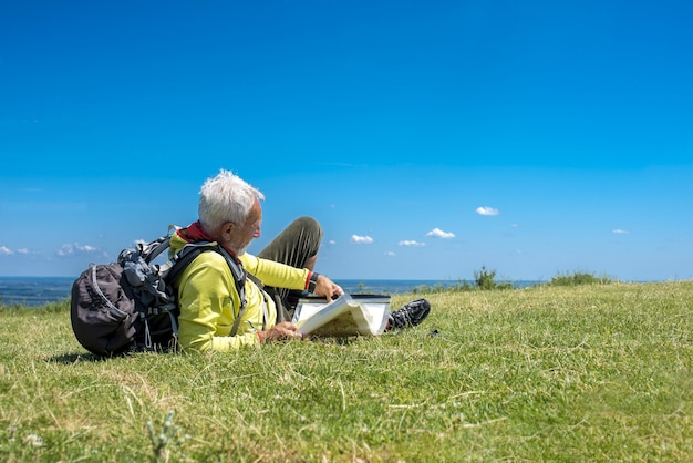 Old male hiker lying in a meadow and looking at a map