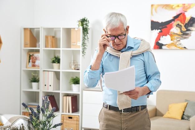 안경과 캐주얼웨어를 입은 노인 남성 연금 수급자는 가정 환경에서 서류 또는 재무 문서를 살펴 봅니다.