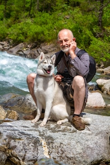 Старик и ездовая собака гуляют возле реки. альпийский пейзаж. активный отдых пенсионера. пожилой мужчина улыбается. прогулка с сибирской лайкой.