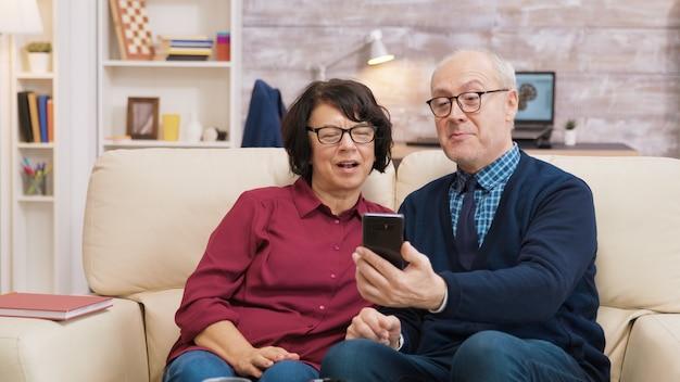 スマートフォンを使ってビデオ通話をしている老人と女性。現代の技術を使用して老夫婦