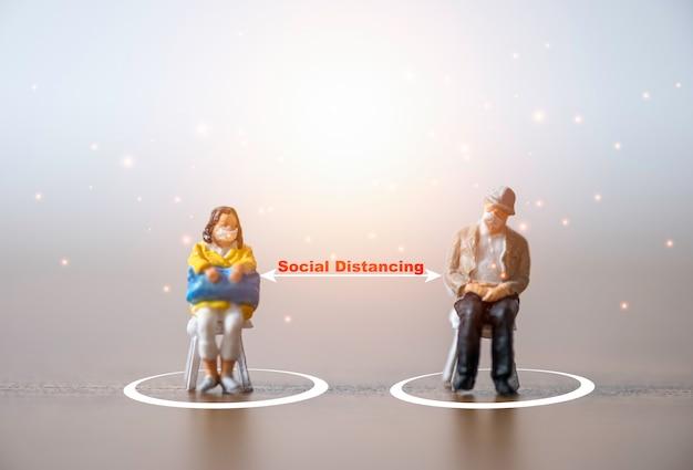 Миниатюрные старики и женщины, носящие маску и садящиеся на стул, держат дистанцию на публике, чтобы предотвратить вспышку коронирусного вируса covid-19, распространяющую пандемическую инфекцию. концепция социального дистанцирования.