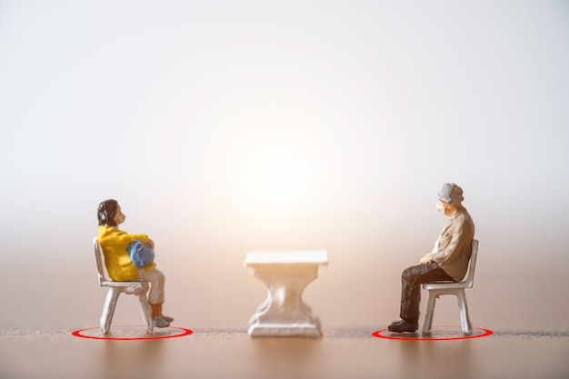 Миниатюрные старики и женщины, носящие маску и садящиеся на стул, держат дистанцию на публике, чтобы предотвратить вспышку коронирусного вируса covid-19, распространяющую пандемическую инфекцию.