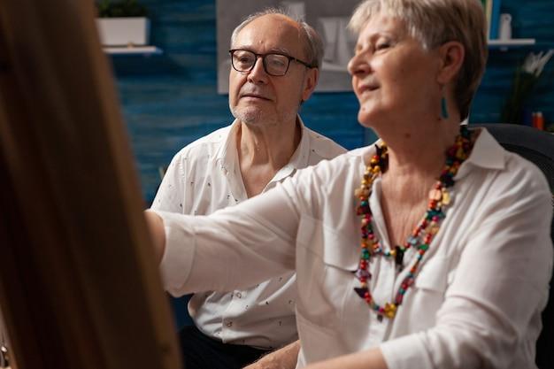 Старик и женщина работают над рисованием вместе
