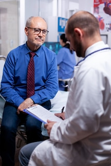 Vecchio che risponde al questionario medico durante l'esame nella stanza d'ospedale hospital