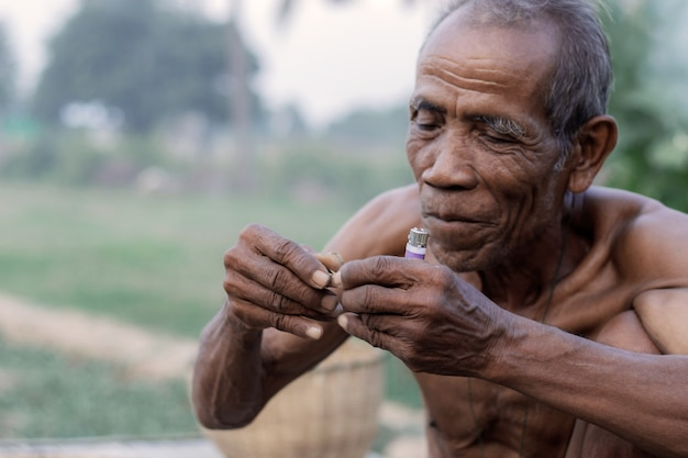 Old man are cigarette in field of thailand.