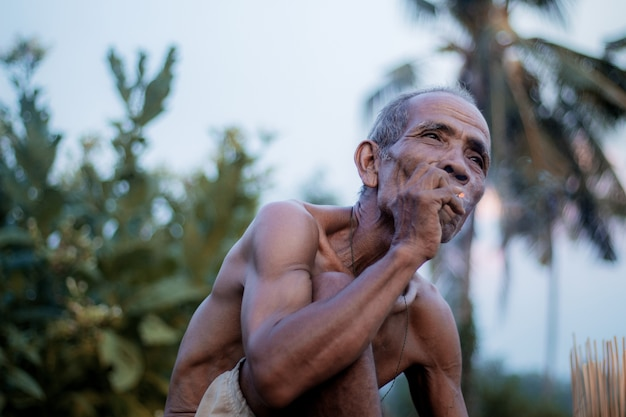 Old man are smoking cigarettes.