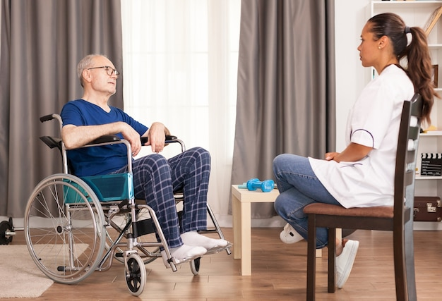 Old man and assistant discussing about his accident and treatment.