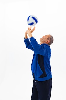 An old man in a blue tracksuit playing ball on white