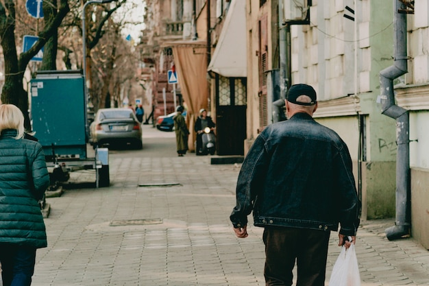 An old man in cap and jeans jacket with white plastic bag walks on the city's street