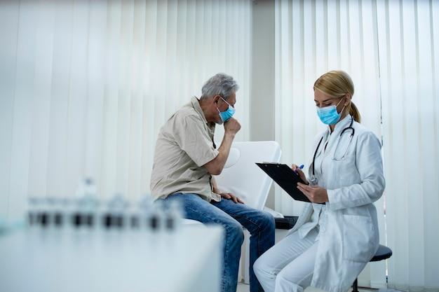 医者がコロナウイルスパンデミックの間に病院のオフィスで症状を書き留めている間に咳をする老人
