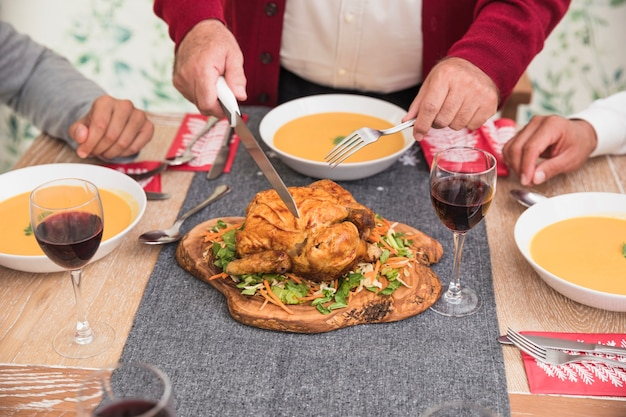Old man cutting baked chicken on festive table
