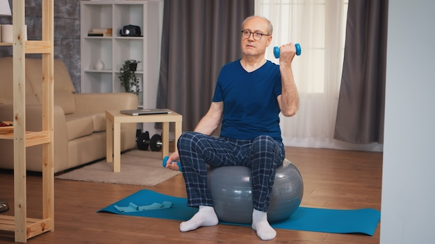 安定ボールにダンベルで上腕二頭筋のトレーニングをしている老人。老人年金受給者が自宅でヘルスケアスポーツを健康的に訓練し、高齢者でフィットネス活動を行う