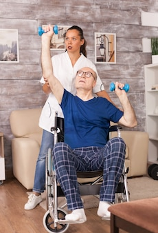 Old man doing exercises during rehabilitation helped by medical worker