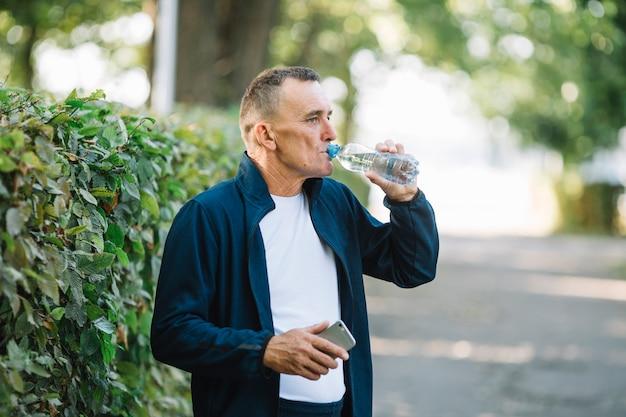 老人は公園で水を飲む
