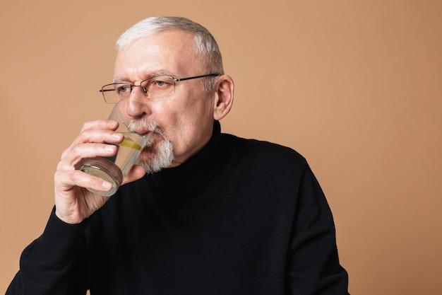 Old man drinking water portrait