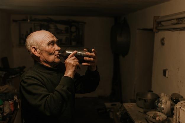 Старик пьет вино из стеклянной бутылки в темном подвале