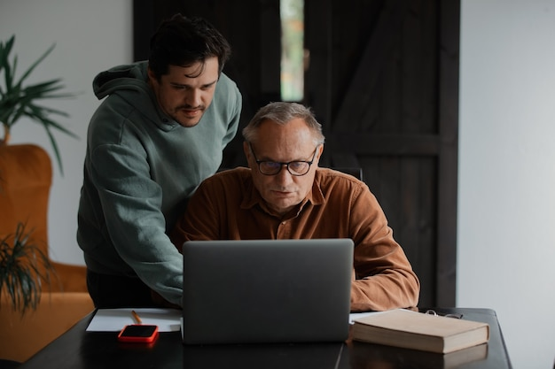 Old man in eyeglasses and his son using laptop computer at home.