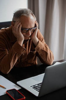 Old man in eyeglasses using laptop computer at home.