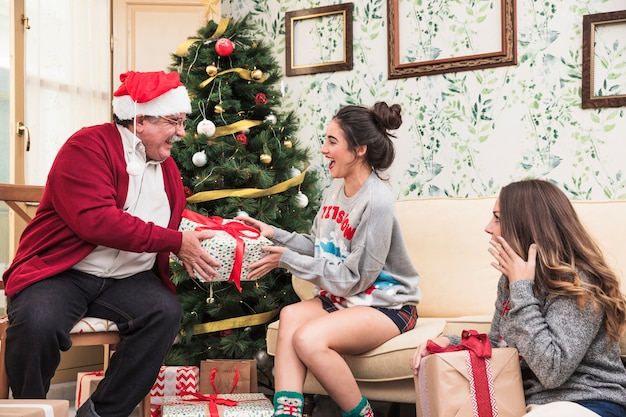 Old man giving big gift box to young woman