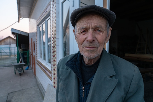 Old man in grey blazer and hat stands near his house