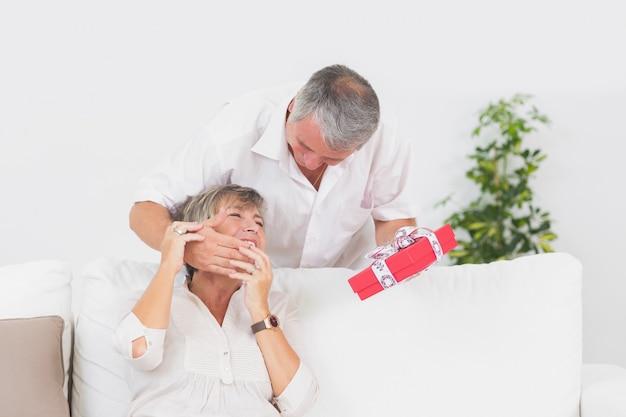선물을주는 그의 아내 눈을 숨기고 노인