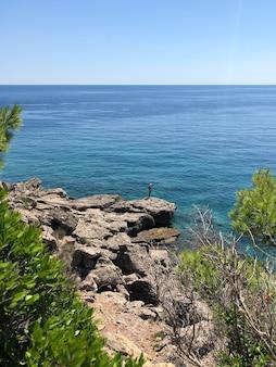 大きな岩石の上に立っている老人の趣味釣り釣り。シニア年金受給者は魚の回転をキャッチします。