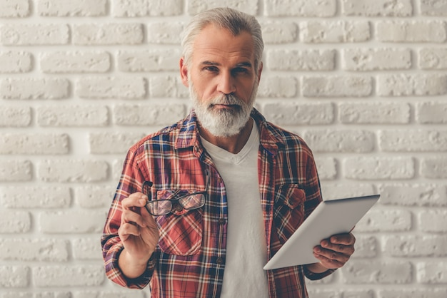 Old man holding a digital tablet and eyeglasses.